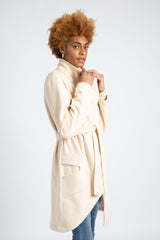 Model is wearing AlekSandraD off-white asymmetrical sweatshirt wrap coat.