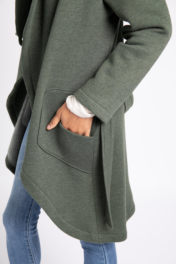 Model is wearing AlekSandraD military green asymmetrical sweatshirt wrap coat.