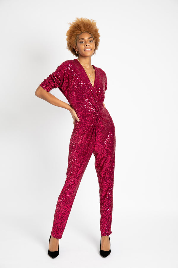 Model is wearing AlekSandraD front knotted sequined jumpsuit.
