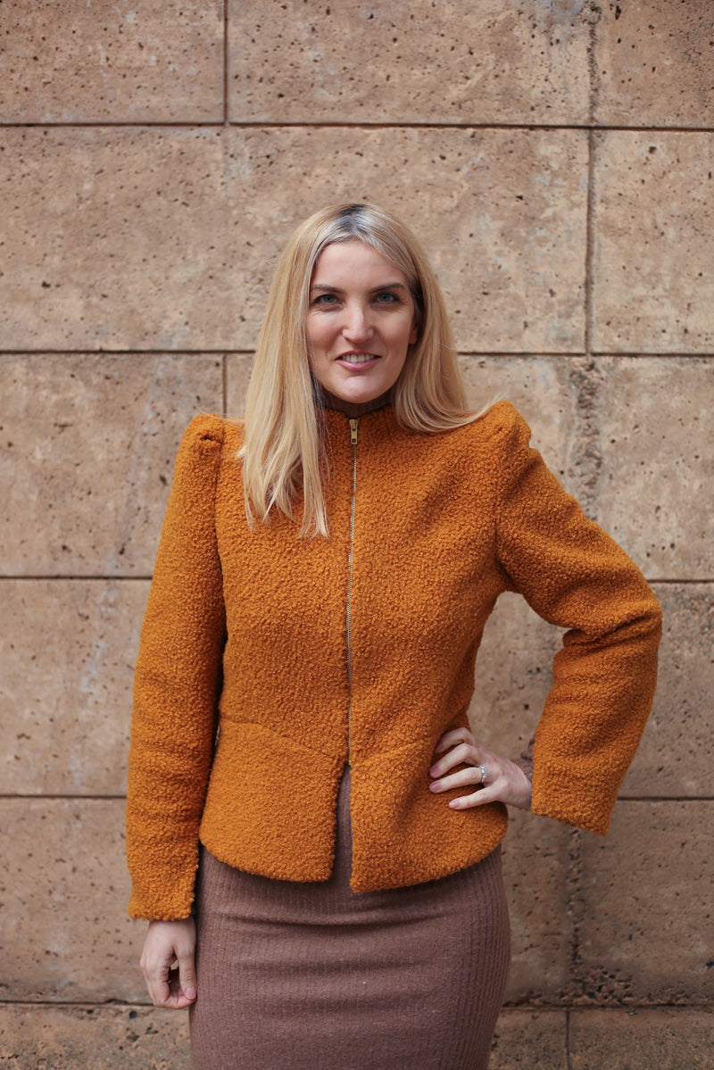 Model is wearing AlekSandraD short orange wool teddy jacket.