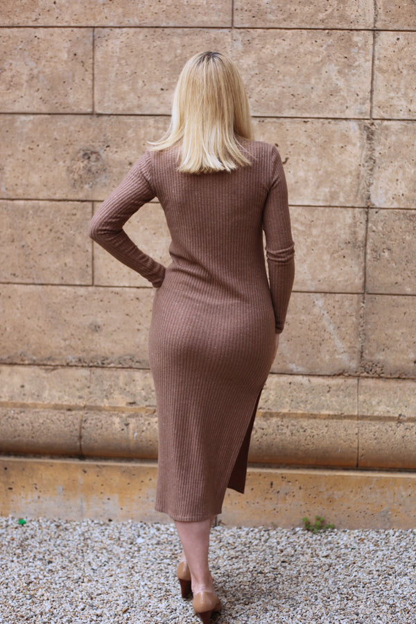 Model is wearing AlekSandraD mocha sweater turtleneck dress with a slit.