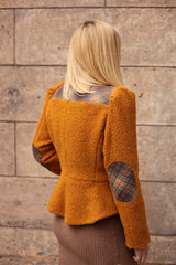 Model is wearing AlekSandraD orange wool teddy jacket with quilted details.