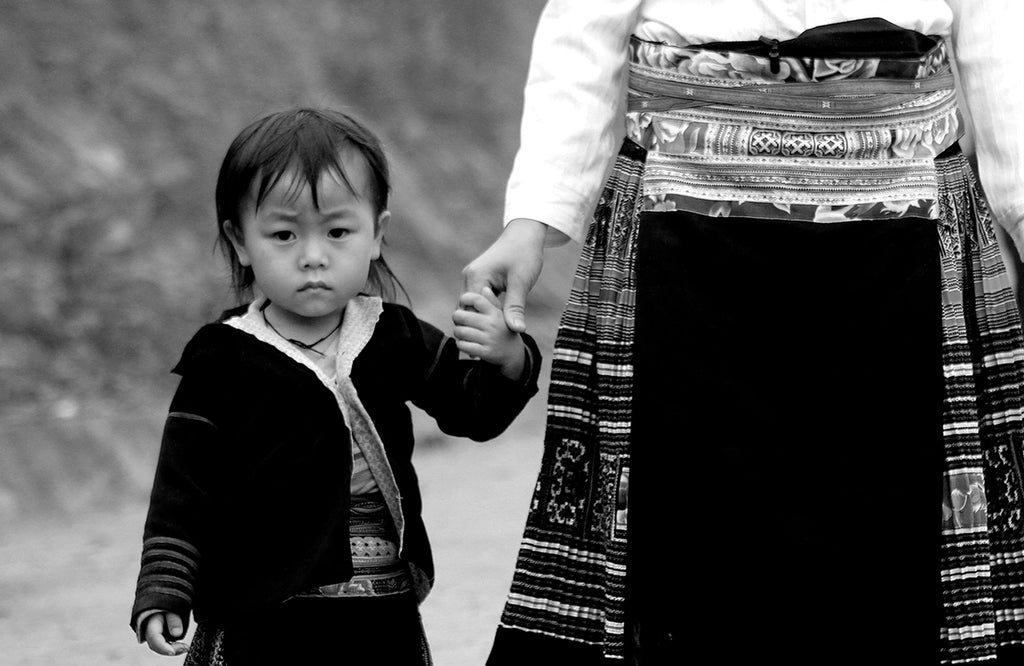 Child in the H'mong Tribe in Northern Vietnam holding hands with mother.