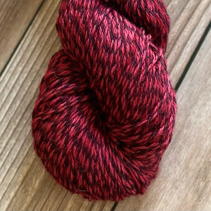 A skein of hand dyed marled peruvian wool yarn in a red color sitting against a wood background