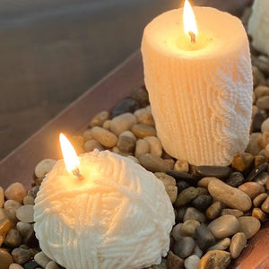 Image of two soy candles with lit wicks, atop of bed of river rocks. One candle is shaped like a ball of yarn. The other is in a pillar shape featuring a cable-knit motif.