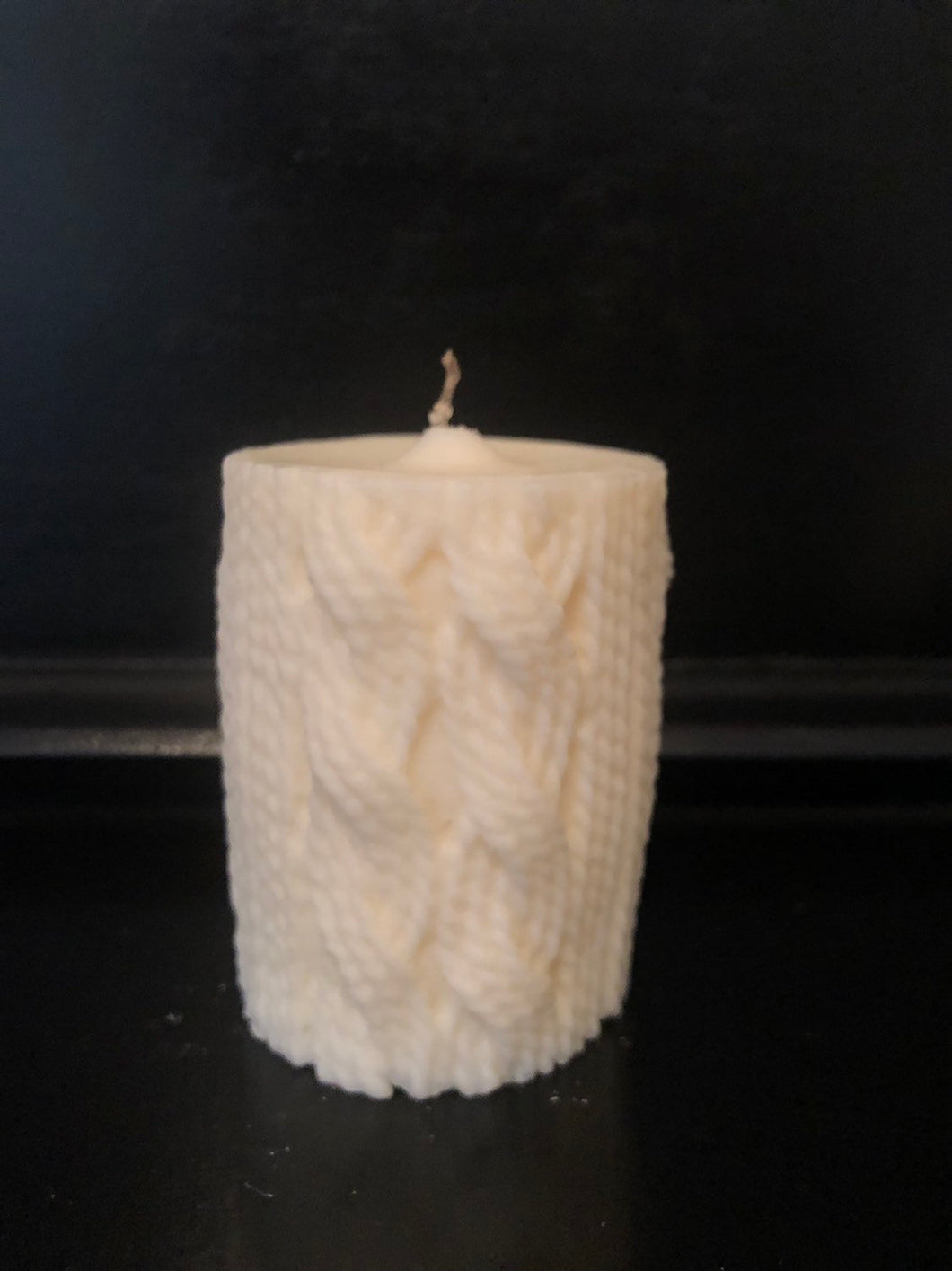 A soy candle in a pillar shape featuring a cable knit motif on the wax, sitting on a black backdrop