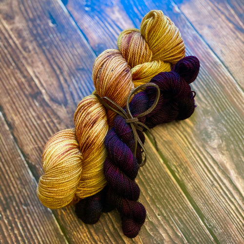A kit of one full skein of wool and nylon dyed to a sunset yellowish orange with splashes of rust, held with two mini skeins of deep red wine, tied together with a leather ribbon, sitting against a wood background.