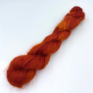 A skein of hand dyed kid mohair and silk yarn in a rust orange  color