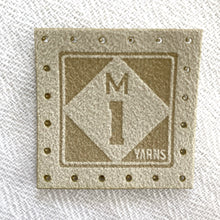 Load image into Gallery viewer, Afaux suede logo tag featuring a roadside sign style logo for the M1 Yarns brand, which features the letter M on top of the number 1 in a diamond shape against a square. The material of these tags are made of faux suede in a cream  tone. One tag has perforations to sew the tag on.