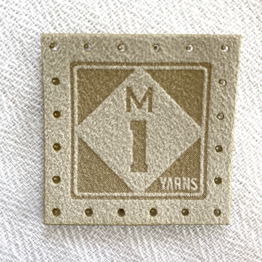 Afaux suede logo tag featuring a roadside sign style logo for the M1 Yarns brand, which features the letter M on top of the number 1 in a diamond shape against a square. The material of these tags are made of faux suede in a cream  tone. One tag has perforations to sew the tag on.