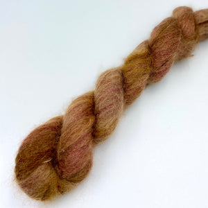 A skein of hand dyed kid mohair and silk yarn in a reddish brown  color
