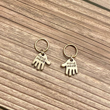 "Load image into Gallery viewer, Two silver toned charms in the shape of hands featuring the words ""Hand made"" engraved in the metal charm. Each charm is attached to a silver toned 10mm hoop -  which can be used as stitch markers on fiber art projects. These charms sit atop a wood background."