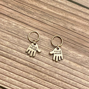 "Two silver toned charms in the shape of hands featuring the words ""Hand made"" engraved in the metal charm. Each charm is attached to a silver toned 10mm hoop -  which can be used as stitch markers on fiber art projects. These charms sit atop a wood background."