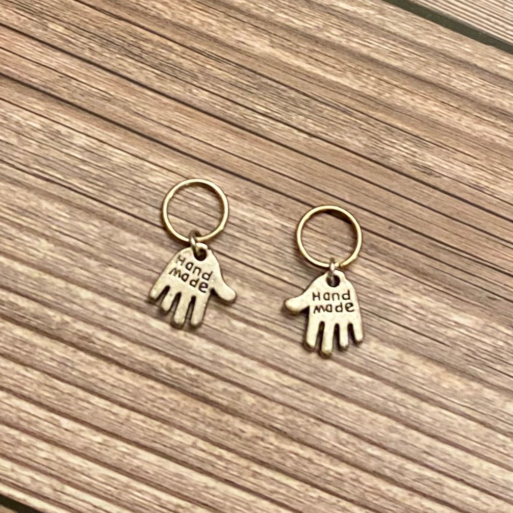 Two silver toned charms in the shape of hands featuring the words
