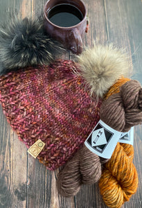 Image of knit hat in brown and red tones, sitting on a wood background with a fur pom pom affixed to the top of the hat with another fur pom to the side of the hat, along with a cup of coffee and two skeins of hand dyed wool yarn, one in a soft brown color and the other in an orange tone. The knit hat features a faux suede logo tag with the M1 Yarns logo, a square with a diamond inside (in a road sign style) with an M on top of the number 1.