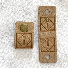 Load image into Gallery viewer, Two faux suede fold-over logo tags featuring a roadside sign style logo for the M1 Yarns brand, which features the letter M on top of the number 1 in a diamond shape against a square. The material of these tags are made of faux suede in tan tones. The tag features a brass screw on tack that is inserted through a hole in the tag to affix the tag to a hat or sweater.