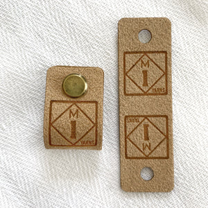 Two faux suede fold-over logo tags featuring a roadside sign style logo for the M1 Yarns brand, which features the letter M on top of the number 1 in a diamond shape against a square. The material of these tags are made of faux suede in tan tones. The tag features a brass screw on tack that is inserted through a hole in the tag to affix the tag to a hat or sweater.