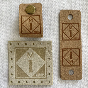 Three faux suede logo tags featuring a roadside sign style logo for the M1 Yarns brand, which features the letter M on top of the number 1 in a diamond shape against a square. The material of these tags are made of faux suede in cream and tan tones. One tag has perforations to sew the tag on. The other features a brass screw on tack that is inserted through a hole in the tag to affix the tag to a hat or sweater.