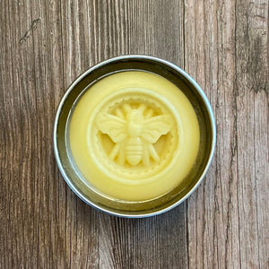 A metal tin holding a round organic lotion bar with a bee motif in the center, sitting on a wood background