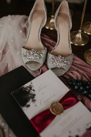 wedding invitation, wedding shoes, wedding decorations laid out on table