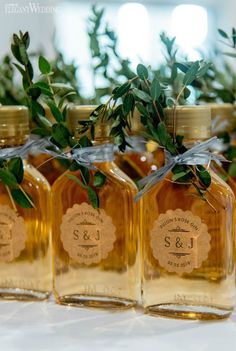 corked bottles of maple syrup or alcohol tied with jute twine and sprigs of fresh greenery. Beautiful wedding favours toronto ontario durham region gta event wedding microwedding planner