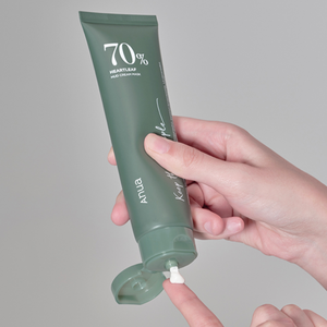 hand squeezing creamy anua 70% heartleaf mud cream mask out of its dark green tube onto finger.