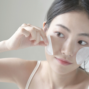 Woman placing cotton pads soaked in anua heartleaf soothing toner on face.