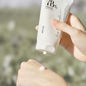 White tube of anua soothing cream opened and squeezed on hand