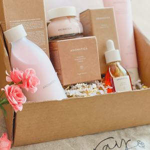 kraft box full of pink Aromatica rose line skincare products.