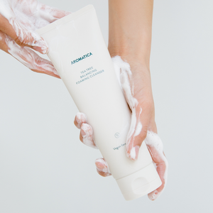 Hands covered in foamy Aromatica tee tree balancing foaming cleanser holding beige bottle of the cleanser
