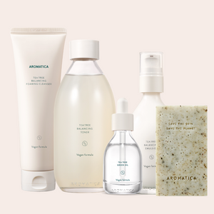 aromatica tea tree products set including a beige cleanser, beige toner in glass bottle, oil in glass bottle, and emulsion with pump in glass bottle.