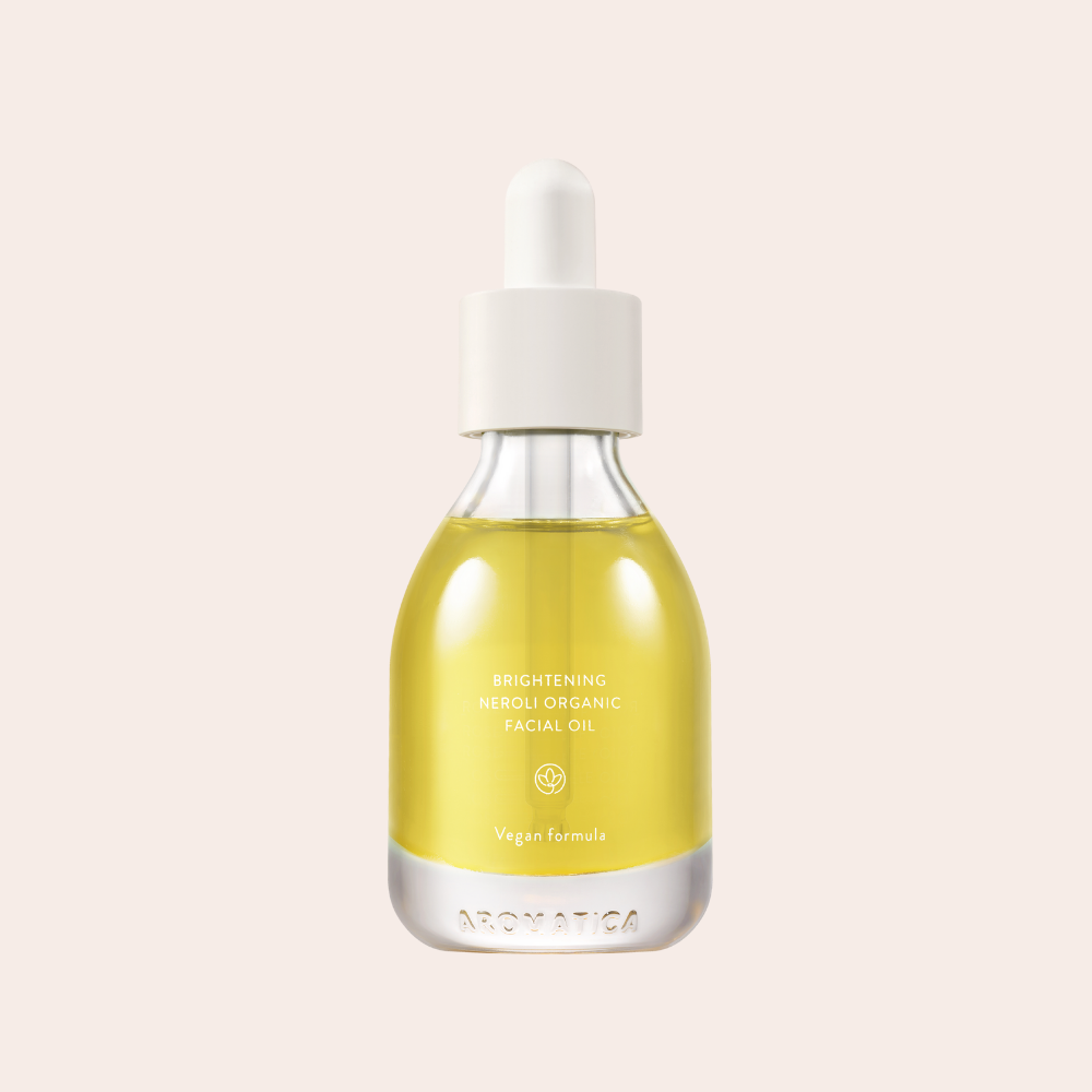 Golden aromatica brightening neroli oil in small glass bottle with dropper.