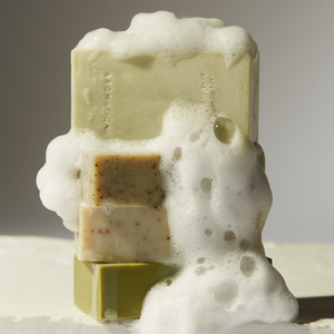 Multiple types of Aromatica Cleansing bars shown with soap foam.
