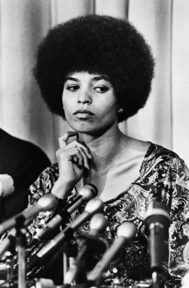 Angela Davis looking thoughtful at a podium
