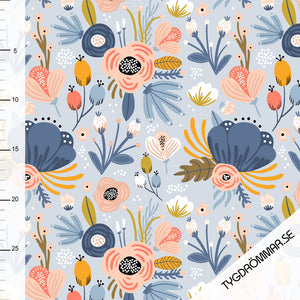 Stock image of Tygdrommar organic jersey cotton knit fabric in Milla Light blue. Light blue backround with floral print in shades of peaches and pinks,blues, greens and yellows