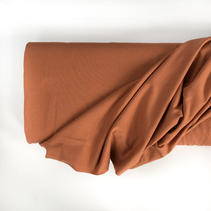 Photo of a roll of Family Fabrics solid cotton jersey cotton knit fabric in colour pecan. A medium brown colour