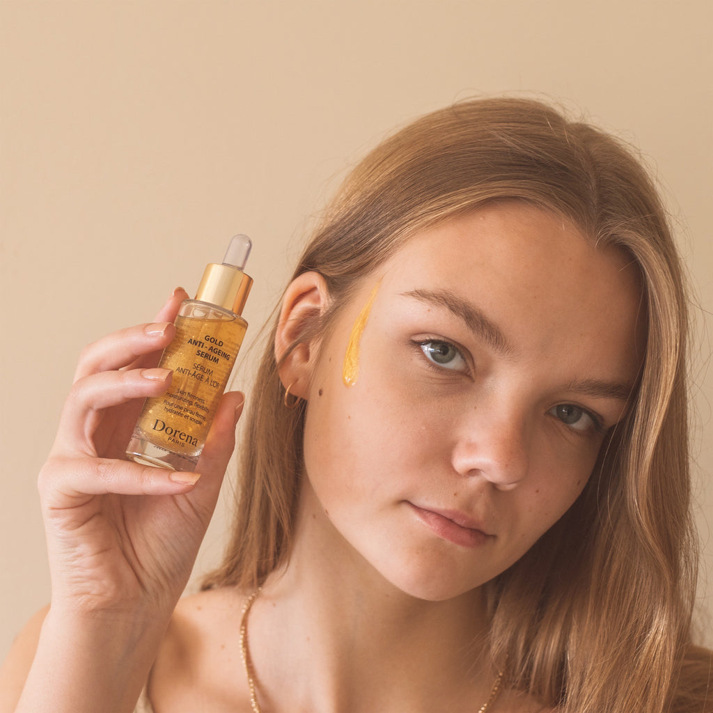 Gold anti ageing serum in a hand of young women model, serum made in France by Dorena Cosmetics