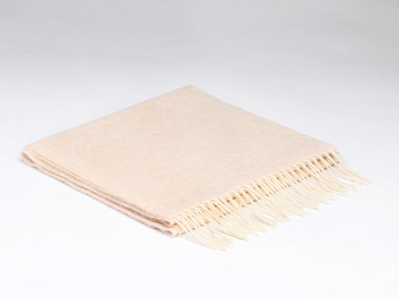 A folded pale cream scarf with white fringe on the ends.