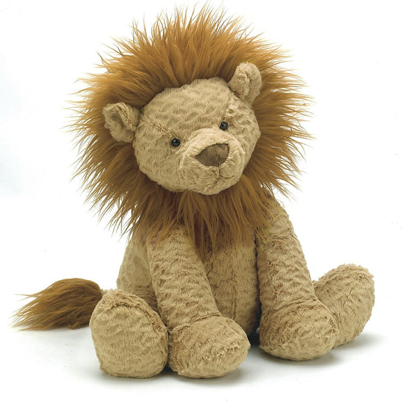 A soft, sandy brown toy lion sitting upright. It has has a hairy brown mane and tuft at the end of its tail.