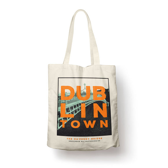 A tote bag with a stylised image of the Ha'Penny Bridge in the centre. The bridge is coloured a pale mint green, the sky cream, and the rest black. 'Dublin Town' is printed in large orange capitals letters over top, taking up most of the print. The title is underneath.