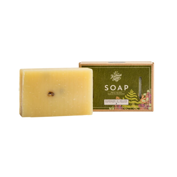 A cardboard box with a dark green square on the front. The logo for the company and scent is on the box, with a flower illustration in two of the corners. Beside is a pale cream rectangular bar of soap with some slightly mottled natural colouring.