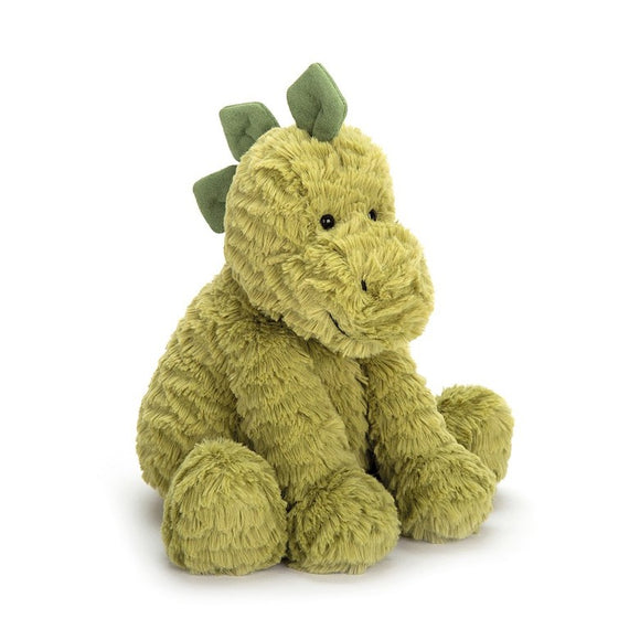 A soft, green toy dinosaur sitting upright. It has three dark green spine plates on its head. It doesn't have a tail.