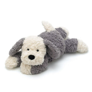 A soft, grey and white toy dog lying on its stomach.