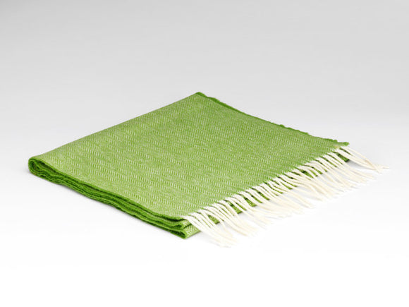 A folded grass green scarf with white fringe on the ends. There is a herringbone pattern across the scarf.