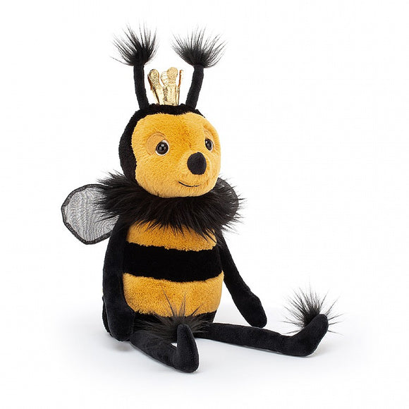 A soft, yellow and black toy bee with long limbs and small wings. There are tufts of black hair on their feet, around the neck and on top of the antennae. There is a small gold crown on their head.