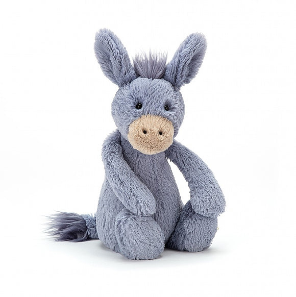 A grey soft donkey toy sitting upright. They have a matching tuft of hair between their ears and at the end of their tail.
