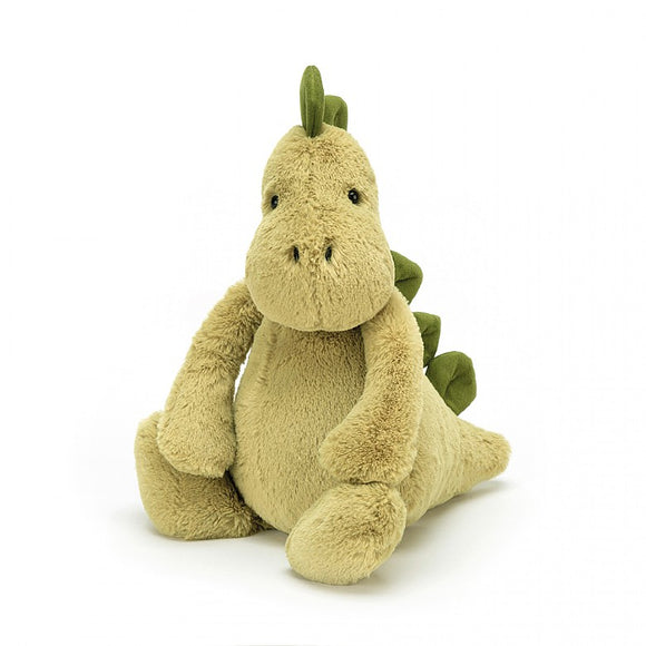 A light green soft dinosaur toy sitting upright. They have soft, dark green spine plates from the top of their head to their tail.