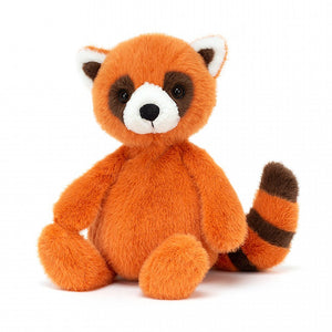 A soft, orangey red toy red panda sitting upright. It has a brown stripped tail, a white snout and brown eyes.