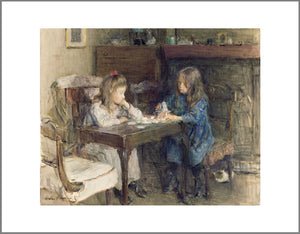 Two young girls sit at a table. Playing cards are scattered across the table and one of the girls is stacking the cards to make a house.