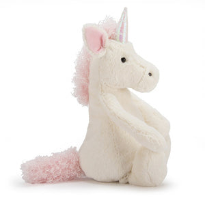 A soft, white toy unicorn sitting upright, facing to the side. It has pink, curly hair for its mane and tale. It's horn is a smoother, iridescent white and pink material.